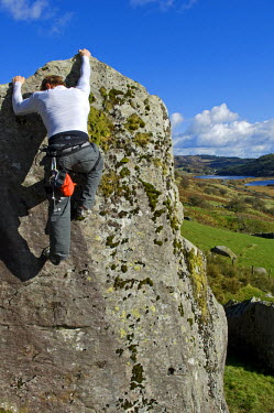 WAL7114 UK, North Wales, Snowdonia.  A man rock climbing on a large granite boulder near Snowdon.  (MR)