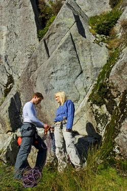 WAL7115 UK, North Wales, Snowdonia.  A man and woman rope up ready to go rock climbing.  (MR)