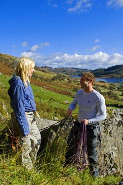 WAL7116 UK, North Wales, Snowdonia.  A man and woman rope up ready to go rock climbing.  (MR)