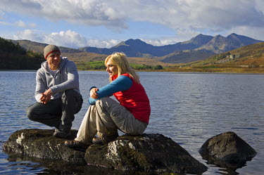 WAL7117 UK, North Wales, Snowdonia.  Man and woman relax on rocks at the edge of Llyn Mymbyr with the backdrop of The Snowdon Horseshoe. (MR)