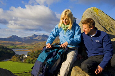 WAL7118 North Wales, Snowdonia.  Man and woman sitting on rocks against the backdrop of Mt Snowdon. (MR)