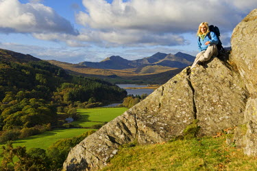 WAL7119 North Wales, Snowdonia.  Woman sitting on rocks against the backdrop of Mt Snowdon. (MR)