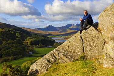 WAL7120 North Wales, Snowdonia.  Man sitting on rocks against the backdrop of Mt Snowdon. (MR)