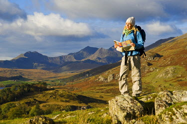 WAL7121 North Wales, Snowdonia.  A woman stop to look at the map whilst hiking in Snowdonia.  (MR)