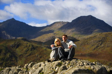 WAL7175 UK, North Wales, Snowdonia.  Couple sit on a rock in front of the Snowdon Horseshoe.  (MR)