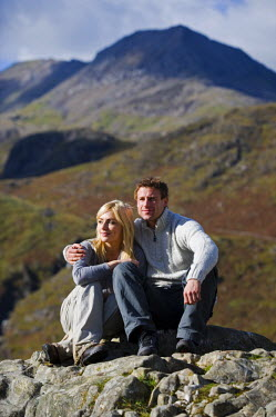 UK, North Wales, Snowdonia. Couple sit on a rock in front of the Snowdon Horseshoe. (MR)