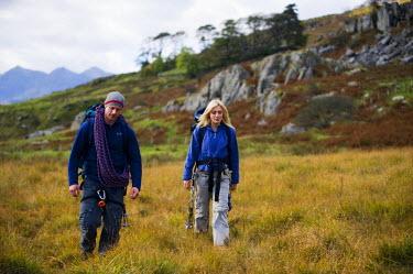 WAL7178 UK, North Wales, Snowdonia.  Man and woman in climbing harness.  (MR)