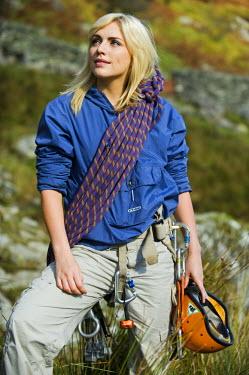 WAL7180 UK, North Wales, Snowdonia.  Woman in climbing harness ready to rock climb.  (MR)