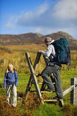 WAL7183 UK, North Wales, Snowdonia.  Man climbs a style in Snowdonia National Park. (MR)