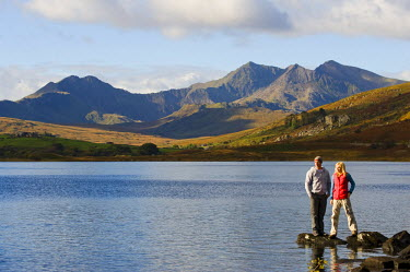 WAL7186 UK, North Wales, Snowdonia.  Man and woman stand on rocks at the edge of Llyn Mymbyr with the backdrop of The Snowdon Horseshoe. (MR)