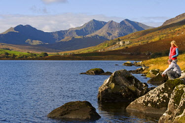 WAL7187 UK, North Wales, Snowdonia.  Man and woman stand on rocks at the edge of Llyn Mymbyr with the backdrop of The Snowdon Horseshoe. (MR)