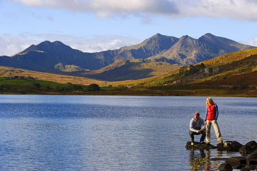 WAL7188 UK, North Wales, Snowdonia.  Man and woman stand on rocks at the edge of Llyn Mymbyr with the backdrop of The Snowdon Horseshoe. (MR)