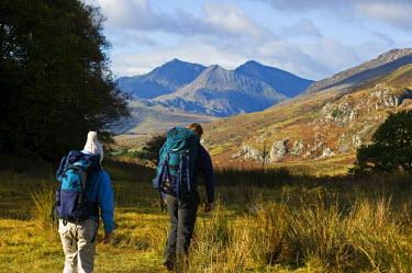 WAL7190 North Wales, Snowdonia.  Man and woman trekking towards Capel Curig. (MR)