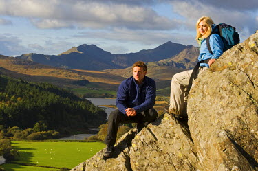 WAL7196 North Wales, Snowdonia.  Man and woman sitting on rocks against the backdrop of Mt Snowdon. (MR)
