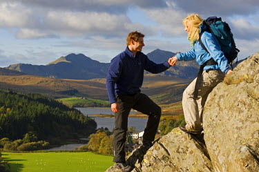WAL7197 North Wales, Snowdonia.  Man and woman scrambling on rocks against the backdrop of Mt Snowdon.  (MR)