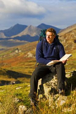WAL7205 North Wales, Snowdonia.  A man stops to look at hisr map whilst hiking in Snowdonia.  (MR)