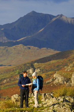 WAL7207 North Wales, Snowdonia.  A man and woman stop to look at their map whilst hiking in Snowdonia.  (MR)