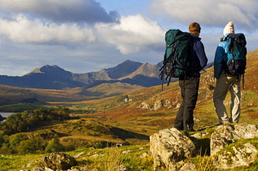 WAL7208 North Wales, Snowdonia.  A man and woman stop to look at their map whilst hiking in Snowdonia.  (MR)