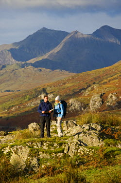 WAL7211 North Wales, Snowdonia.  A man and woman stop to look at their map whilst hiking in Snowdonia.  (MR)