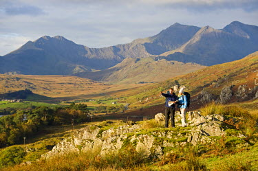 WAL7212 North Wales, Snowdonia.  A man and woman stop to look at their map whilst hiking in Snowdonia.  (MR)