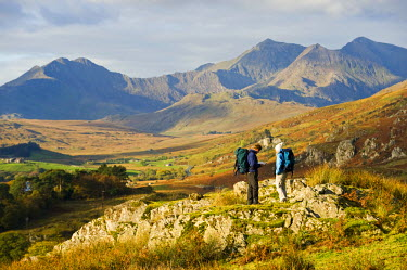 WAL7213 North Wales, Snowdonia.  A man and woman stop to look at their map whilst hiking in Snowdonia.  (MR)