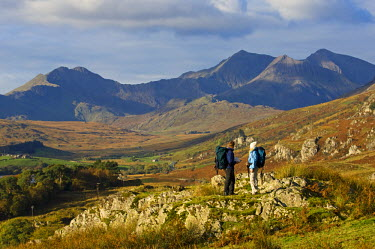 WAL7214 North Wales, Snowdonia.  A man and woman stop to look at their map whilst hiking in Snowdonia.  (MR)
