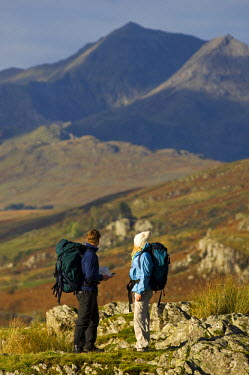WAL7215 North Wales, Snowdonia.  A man and woman stop to look at their map whilst hiking in Snowdonia.  (MR)