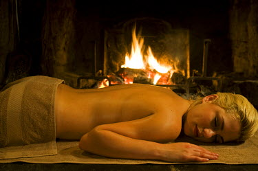 Gilar Farm, Snowdonia, North Wales. A girl relaxes after a massage in front of the open fire. (MR)