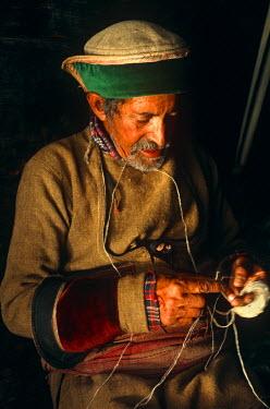 IND6233 India, Himachal Pradesh, Kinnaur, Baspa Valley, Kamru. A Kinnauri man wearing a traditional Kinnauri hat prepares skeins of wool for weaving.
