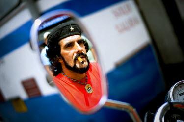 AR3076600005 Che Guevara impersonator smokes a cigar in Venezuela