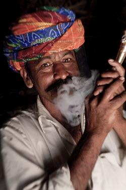 IN02168 Indian man (member of Bishnoi religous sect) smoking a pipe, nr Jodhpur, Rajasthan, India