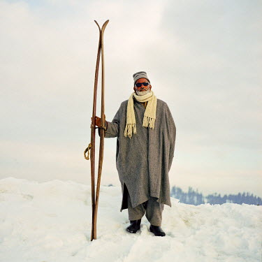 AR3237600013 An old Kashmiri ski guide holds a pair of wooden skis, Kashmir, India