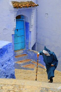 MOR1929AW An old man walking through the bluish Chefchaouen medina. Morocco