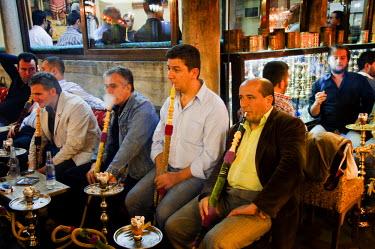 TUR0151AW Men smoking nargileh and taking tea at Corlulu Alipasa Medresesi. Istanbul, Turkey