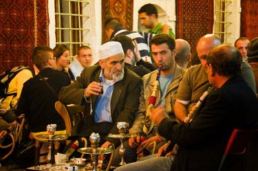 TUR0150AW Men smoking nargileh and taking tea at Corlulu Alipasa Medresesi. Istanbul, Turkey