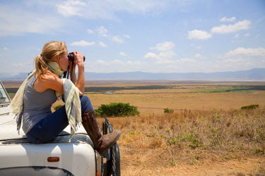 TZ3199 Tanzania, Ngorongoro. A tourist looks out over the Ngorongoro Crater from the bonnet of her Land Rover. MR.