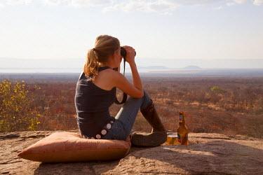 TZ3238 Tanzania, Tarangire. A woman looks out over the Tarangire National Park at sunset. MR.