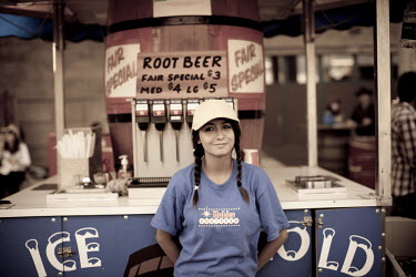 CAN2692AW A young girl selling root beer at a midway concession at the Calgary Stampede, Canada