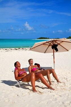 VN01121 Venezuela, Archipelago Los Roques National Park, Cayo de Agua, Tourists sitting under beach umbrella