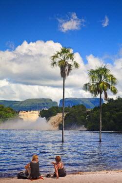 VN01275 Venezuela, Guayana, Canaima National Park, Canaima Lagoon, Tourist on beach looking at Hacha falls