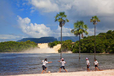 VN01276 Venezuela, Guayana, Canaima National Park, Canaima Lagoon, Schooldgirls playing football on beach infront of Hacha falls