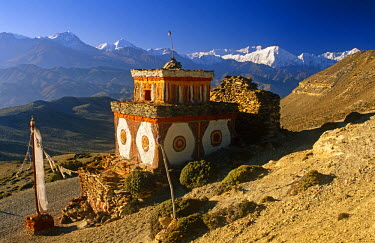 NEP1635 Nepal, Himalaya, Mustang. A decorative chorten, or Buddhist shrine, known as Chhyungkar guards the trail near Syangboche hamlet and the Syangboche Pass while the massive Annapurna massif frames the ho...