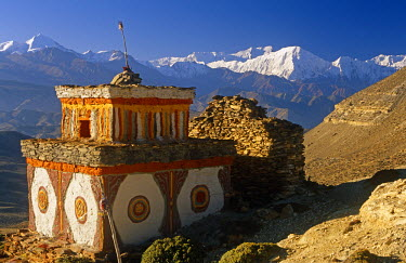 NEP1636 Nepal, Himalaya, Mustang. A decorative chorten, or Buddhist shrine, known as Chhyungkar guards the trail near Syangboche hamlet and the Syangboche Pass while the massive Annapurna massif frames the ho...