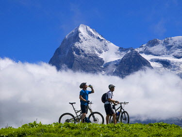 AR3245100004 Grindelwald, Switzerland, Bernese Oberland: Two mountain bikers are resting and drinking near the village of Murren, during a long bike ride in the Bernese Oberland. In the background the famous Eiger...