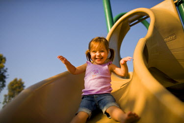 AR3250500012 Newport Beach, USA, California: A young girl with pig tails smiles at the camera as she slides down a slide at a park in Newport Beach, California.