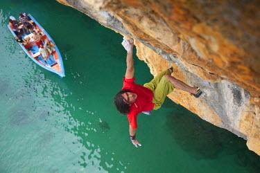AR3309500042 Venezuela; A young man free climbing 40' above the Caribbean