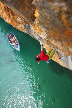 AR3309500044 Venezuela; A young man free climbing 40' above the Caribbean