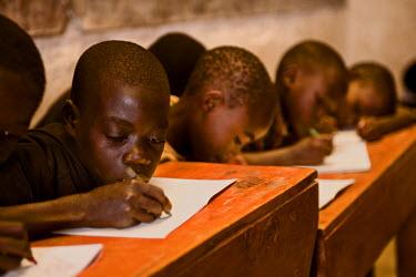 AR3321900018 Rugerero Genocide Survivor's Vil, Rwanda, Gisenyi: Boys work at their desks in a Rwandan school house.
