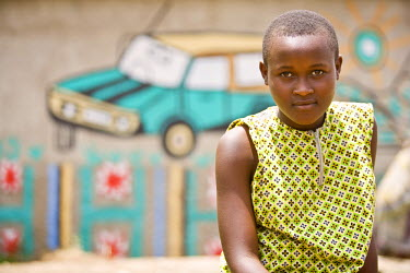 AR3321900004 Rugerero Genocide Survivor's Vil, Rwanda, Gisenyi: A young Rwandan woman before her home in Rugerero.