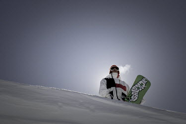 AR3332600023 Vail, USA, Colorado: Portrait of backlit snowboarder standing with board on horizon.